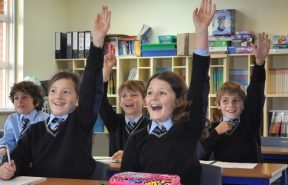 OBH pupils raising their hands and enjoying learning in the beautiful environment
